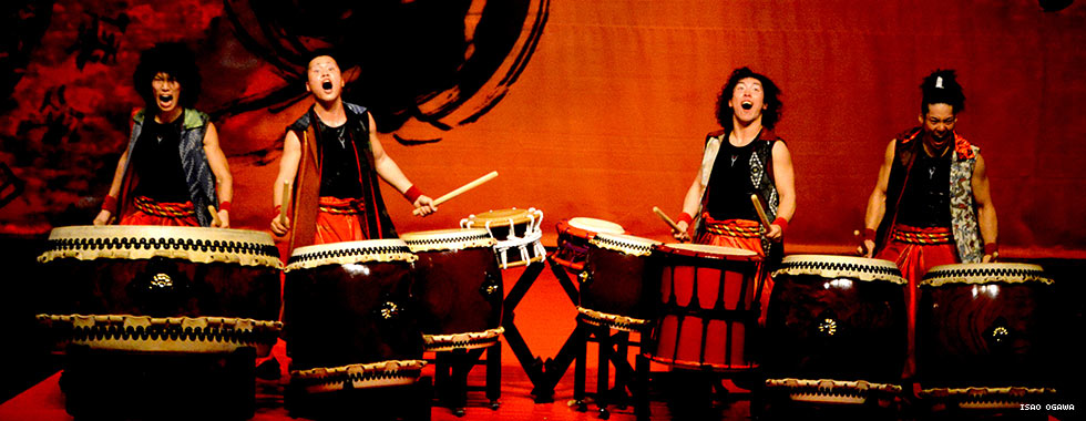 Four percussionists wearing belted pants and decorated vests yell out while they play their giant drum kits.