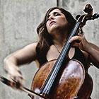 Classical musician Alisa Weilerstein, with her eyes closed and facing upward, performs a piece on her cello.