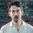 Jazz bandleader and musician Fred Hersch, standing against a distressed brick wall, looks directly at the camera in a portrait shot.