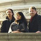 David Finckel, Wu Han, and Philip Setzer stand along an ornate wall and railing wearing coats.