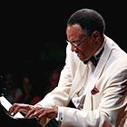 Jazz musician Ramsey Lewis plays the piano in a tuxedo.