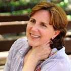 Soprano Dawn Upshaw smiles and rests her left hand on her neck.