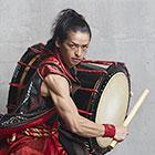 A percussionist flexes his arm muscles as he bangs on a massive drum hanging from his shoulder.