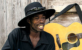 Brushy One String wears a large brimmed hat and sits in front of his guitar with one string.
