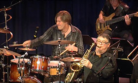 A man plays the drum while another man plays the saxophone to his right.