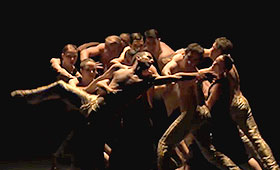 A male dancer extends his arms and legs out while his body is supported by a large group of male and female dancers.