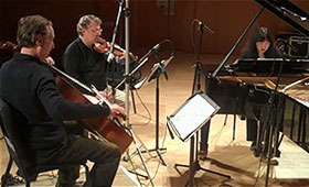 Cellist David Finckel, violinist Philip Setzer, and pianist Wu Han sit close together while they record in a music studio.