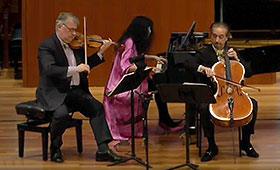 A violinist, pianist, and cellist perform on stage.