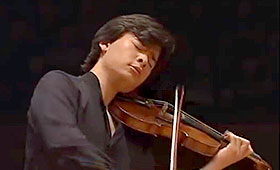 Jackiw closes his eyes and passionately plays the violin on a dark stage.