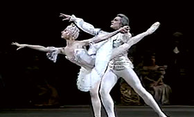 A ballerina reaches forward on one leg while a man supports her.