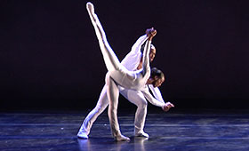 A male dancer supports a female dancer as she leans down toward the stage with a leg extended to the sky.
