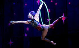 An acrobat stretches through a hoop thathangs from the ceiling