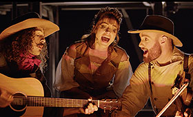 A man with a guitar, a woman, and a mad with a fiddle sing around a campfire.