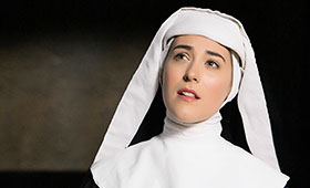 A nun wearing a habit in a dark room looks up while singing.