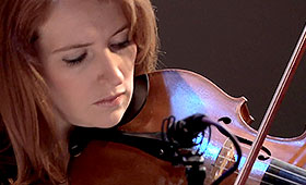 A closeup photo of a red headed woman playing the violin.
