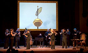 Members of Tafelmusik Baroque Orchestra stand on a stage below an oversized framed picture of a building spire while they perform on their classical instruments.