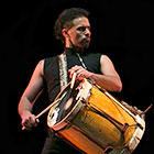 A musician taps his drumsticks on a large drum strapped to his shoulder.
