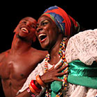 A shirtless male dancer and a female dancer dressed in traditional dress perform with Balé Folclórico da Bahia.