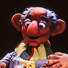A balding, big-eared, larger-than-life puppet depicts the play's title character.