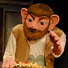 A bearded, big-eared, larger-than-life puppet depicts the play's title character.