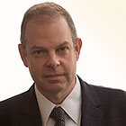 Bill Charlap looks at the camera wearing a suit and tie.