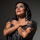Lila Downs, wearing large baubles earrings, crosses her arms across her chest, showing ornate tattoos.