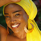 A woman wearing a brightly colored headscarf and large, round earrings, smiles for the camera.