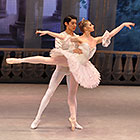 A male dancer holds up a female dancer while she stands and extends her right leg at a 90-degree angle behind her.