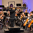 A conductor stands on a pedestal in front of the orchestra.