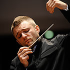 Karabits, eyes closed and dressed in a dark suit, raises his baton and left hand.