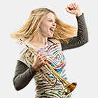 Jazz musician Bria Skonberg, with a look of excitement, holds a trumpet in her right hand and pumps her left fist in the air.
