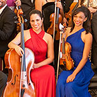 A cellist and violinist from Sphinx Virtuosi dressed in formal attire smile for a pre-performance photograph.