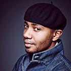 Miller, wearing a denim jacket and dark beret, glances sideways into the camera.