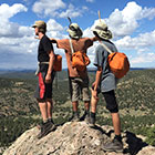 Three young men wearing hiking gear and backpacks stand atop a boulder and look out at the mountains below.