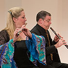O'Connor, dressed in a flowy-armed gown, blows into her flute while Kay, wearing a dark suit, sits to her right and plays his clarinet.