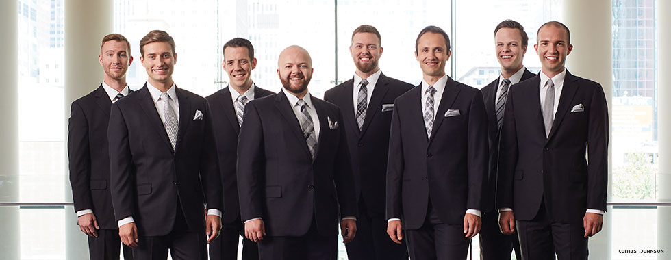 Eight men wearing dark suits stand straight in front of a window and smile for the camera.