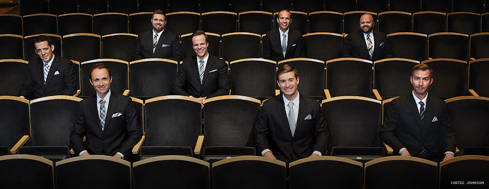 Eight men wearing dark suits smile as they sit randomly spaced in a section of auditorium seating.