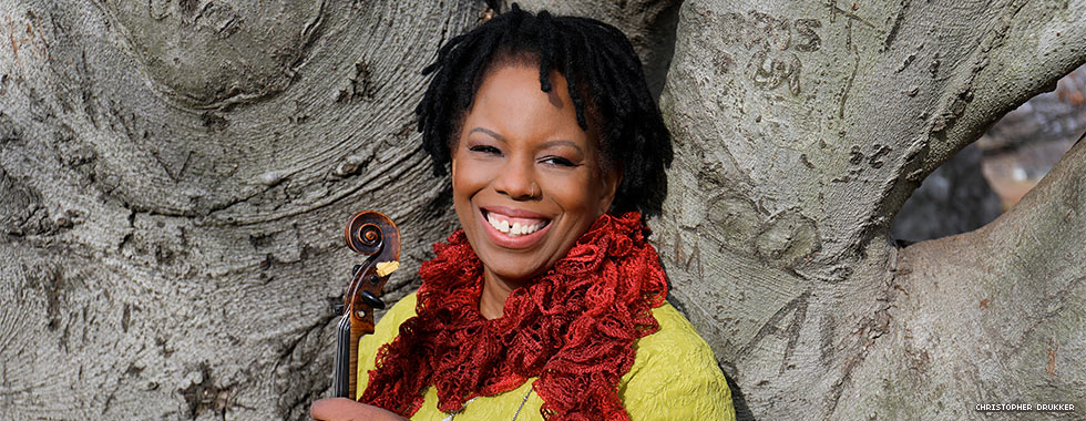 A woman shown from the shoulders up standing against a large tree trunk smiles as she holds her violin.