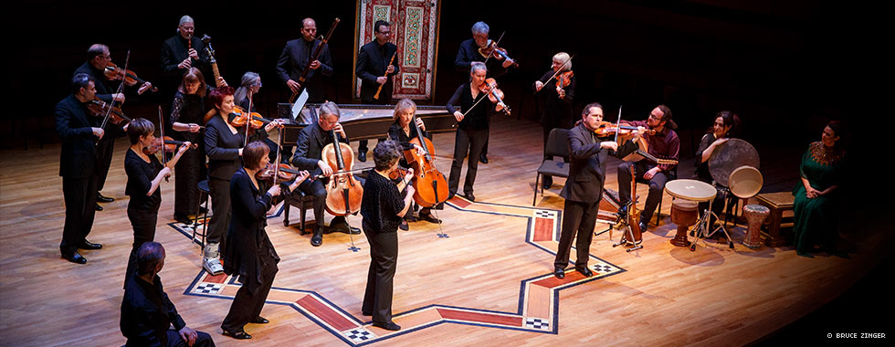 An orchestra arranged sporadically on a stage play their stringed, wind and percussion instruments.