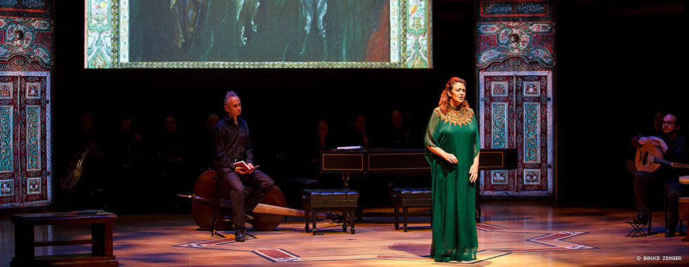 A woman wearing a floor-length flowing gown sings while a musician and a man holding a booklet look on from the shadows.