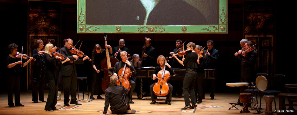 An orchestra performs while a man sitting on the stage floor in front of them watches.