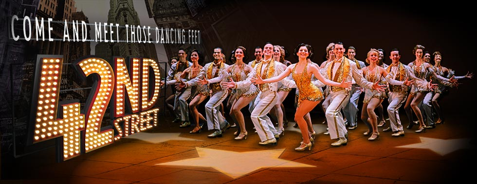 "A logo for ""42nd Street"" and the tagline ""Come and meet those dancing feet"" accompany an image of a group of male and female dancers in tuxedos and glittery mini dresses with their left legs bent in front, right legs bent behind them, and their arms extended from their sides."