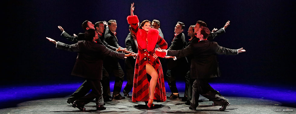 "An actress depicting main character Peggy Sawyer—dressed in a luxurious fur overcoat, her right arm pointed upward, and her left hand on her hip—is surrounded by men in tuxedos with their left arms motioning to her and their right arms extended behind them in a musical number from ""42nd Street."""