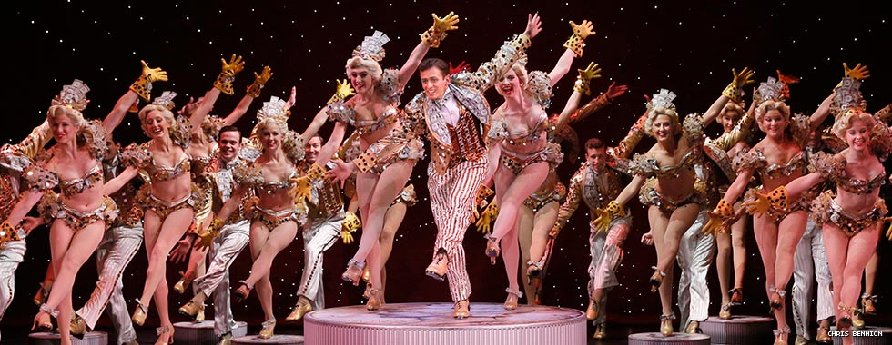 "The cast of ""42nd Street"" wear glittery two-piece costumes and striped tuxedos while they kick their left legs forward and extend their arms up and down."