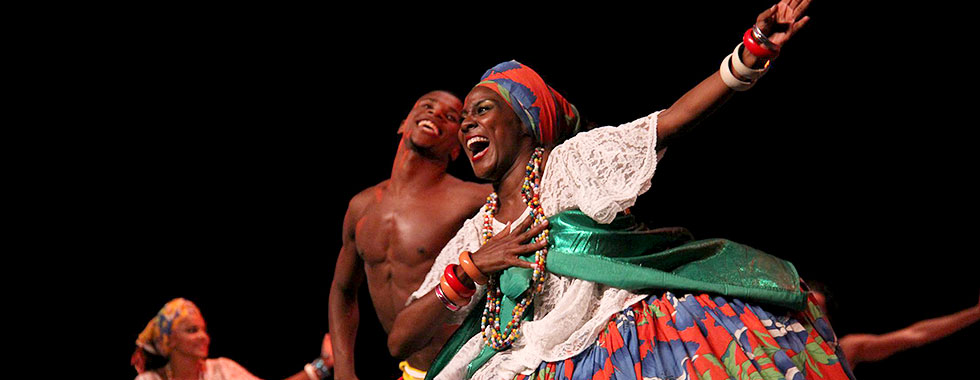 A shirtless male dancer and a female dancer dressed in traditional Brazilian dress perform with Balé Folclórico da Bahia.