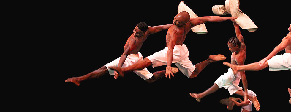 While holding a straw hat in their right hands, three male dancers—shirtless, barefoot, and wearing shorts—leap with their left legs extended forward and their right legs bent back.