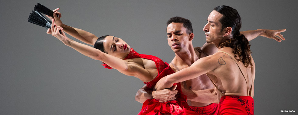 A female dancer leans back and extends her arms straight up while a male dancer on each side wrap their left and right arms around her waist.