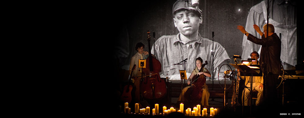 Candles on the stage floor illuminate a conductor leading string musicians while a video screen behind the group shows historic images of coal miners.