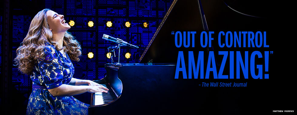 """Out of control amazing!"" - The Wall Street Journal. A woman with long wavy hair and wearing a dress plays a grand piano while she sings."