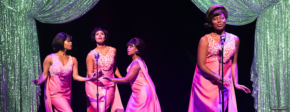 A woman in a cocktail dress and 1960s-era hairstyle sings at a single microphone off to the side while three similarly dressed backup singers dance and croon into their shared mic.